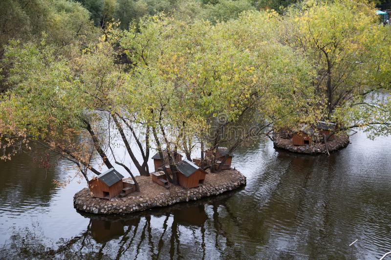Several Islands in the pond, lined with cobblestones, houses for birds, trees. Nature, ecology. Artificial structures stock photography