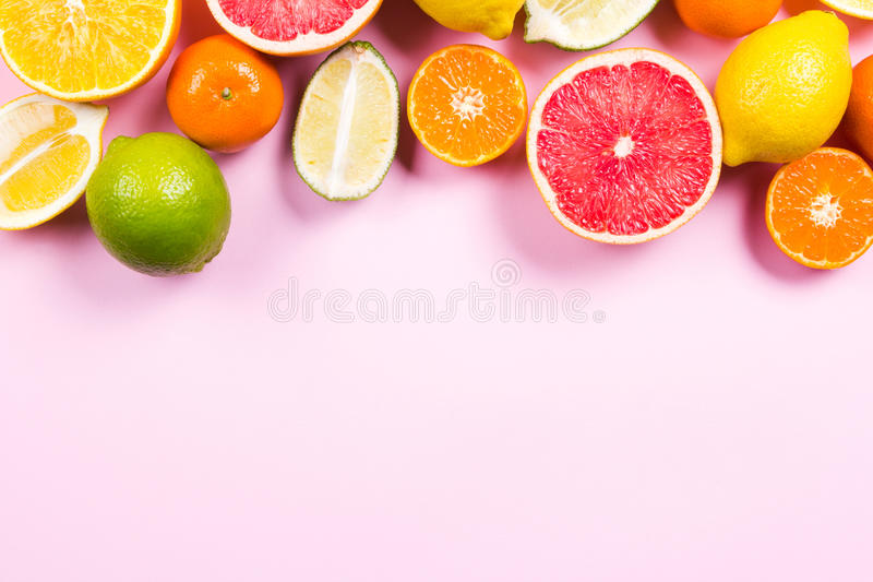 Several kinds of whole and cut citrus on a pink background. Top view stock images