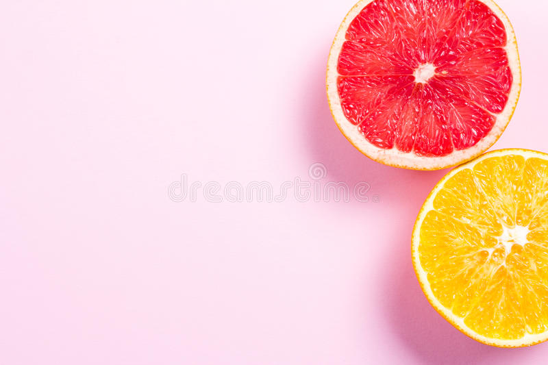 Several kinds of whole and cut citrus on a pink background. Top view royalty free stock photography