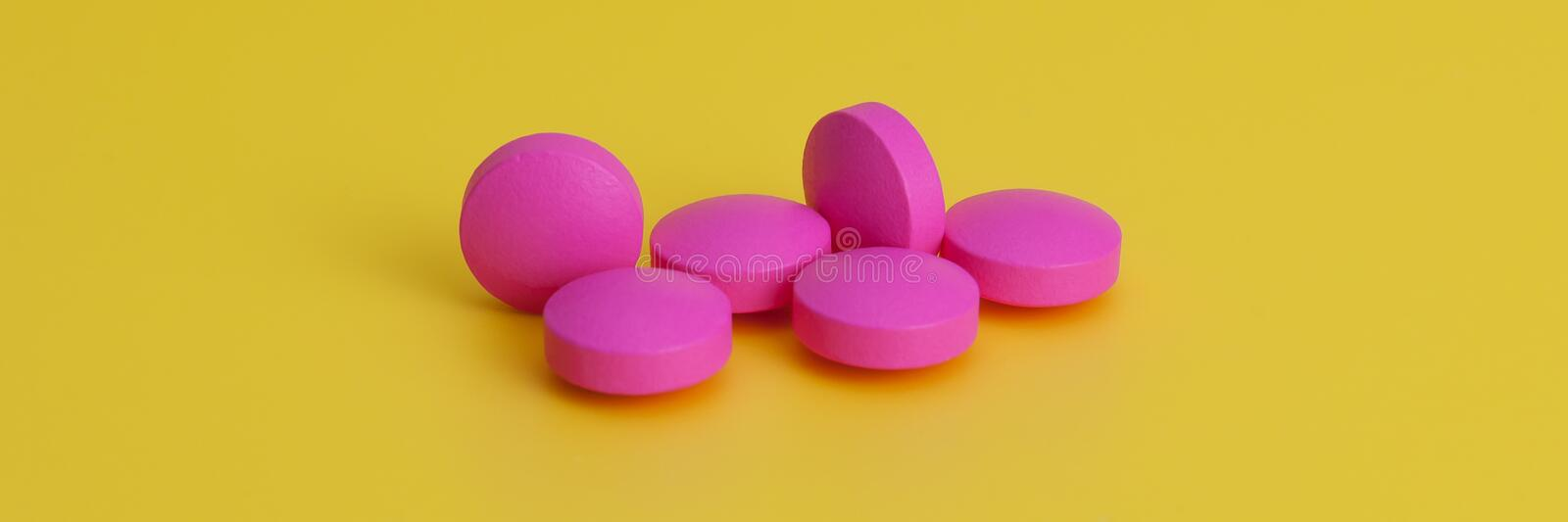 Several large bright pink tablets on a yellow background. In the center of the image. stock photos