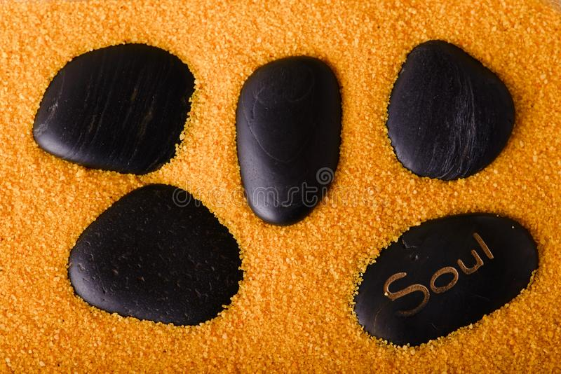 Several lava stones in yellow sand stock photography