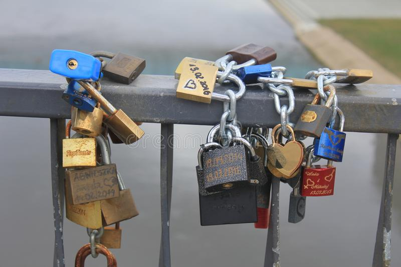 Several locks hanging on the frame of the bridge. As a symbol of forever lasting love and relationship stock photo