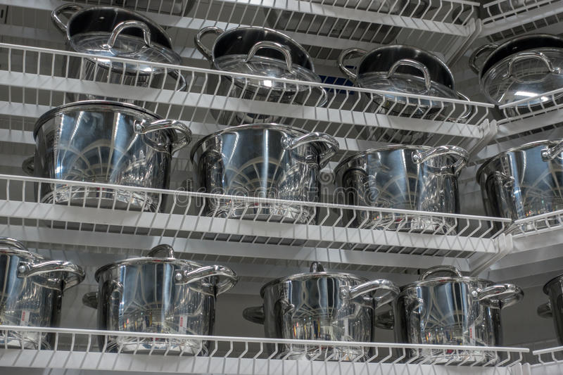 Several metal pans on shelves. This images contains of several metal pans on shelves stock photos