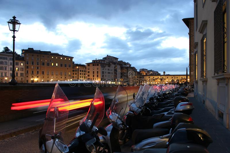 Several motorbikes parked in a row along the street with light trails of a car and cityscape of Florence. With Arno riverfront buildings as background royalty free stock images