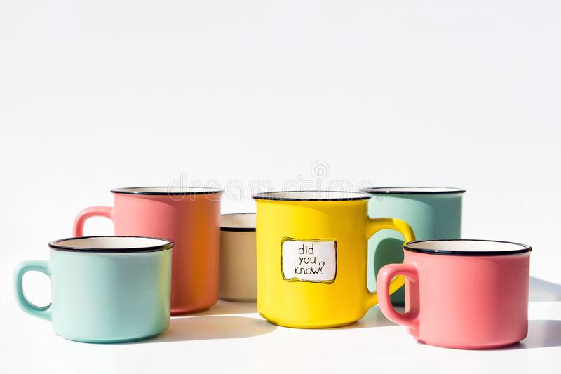 Several multi-colored coffee cups and one with the inscription Did you know. Several multi-colored coffee cups and one yellow with the inscription Did you know royalty free stock photos