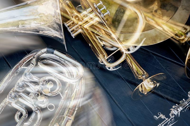 Several musical wind instruments orchestra trumpets, plates, clarinet. Several musical wind instruments orchestra trumpets, plates, clarinet on a dark wooden royalty free stock photography