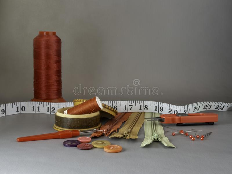 Red cone of thread for sewing, zippers, seamripper and scissors. Several notions for sewing background, with copyspace. Ready for sewing with these notions stock image