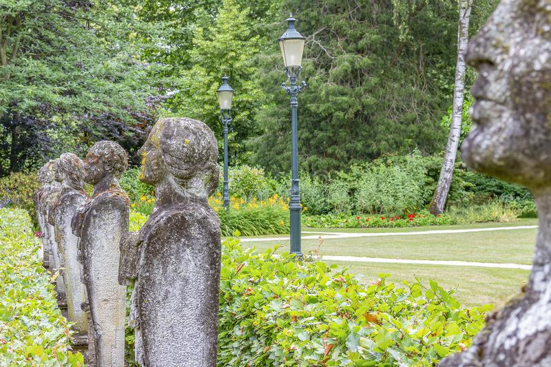 Several old and weathered stone statues of persons on a row landscape photographed in a park or Bouvigne Castle at Breda, Nether. Lands stock photography