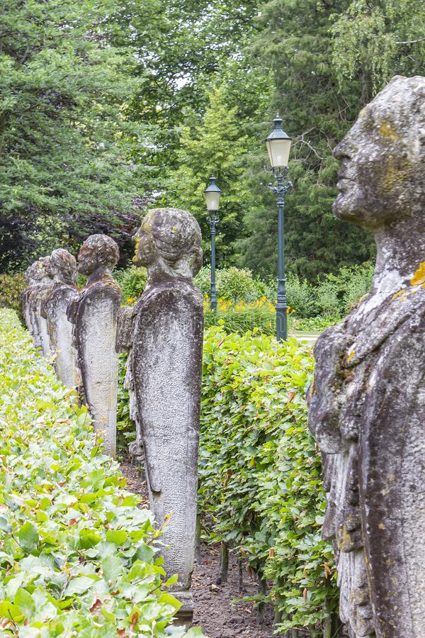 Several old and weathered stone statues of persons on a row portrait photographed in a park or Bouvigne Castle at Breda, Netherl. Ands stock photo