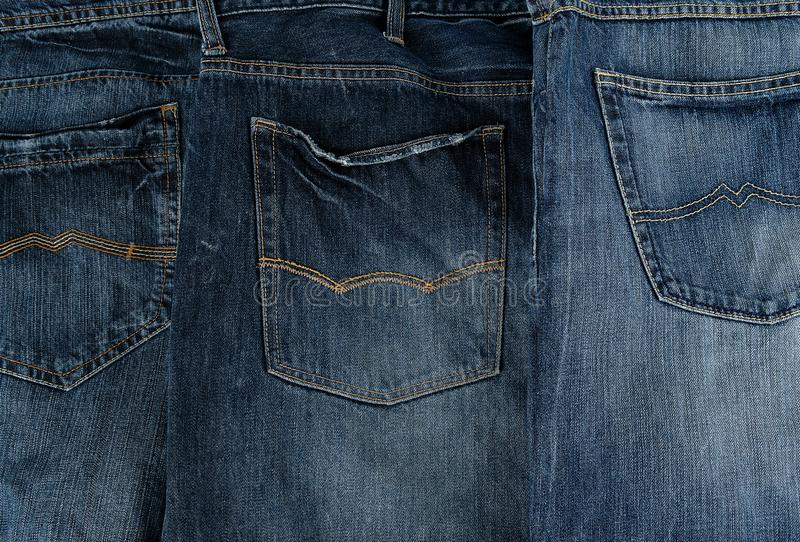 Several other classic jeans folded in a row. Back pocket stock photo
