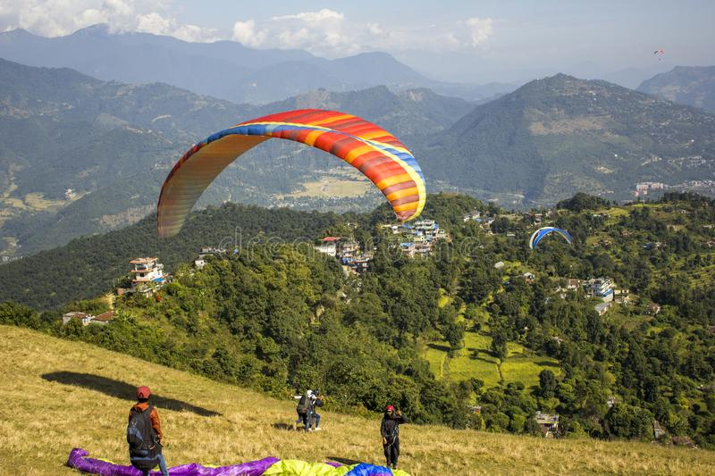 A several paragliders with parachutes on the slope are preparing to fly, tandem runs for takeoff against the backdrop of a green stock photos