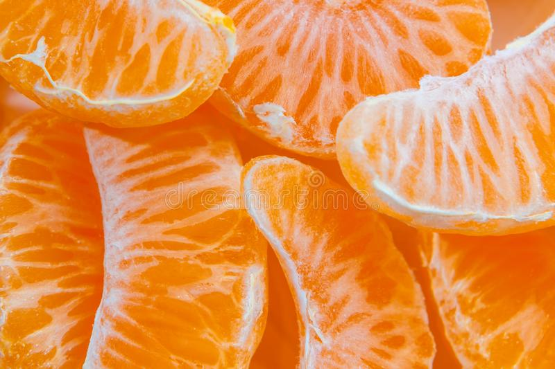 Several peeled ripe Mandarin slices, texture background royalty free stock photography