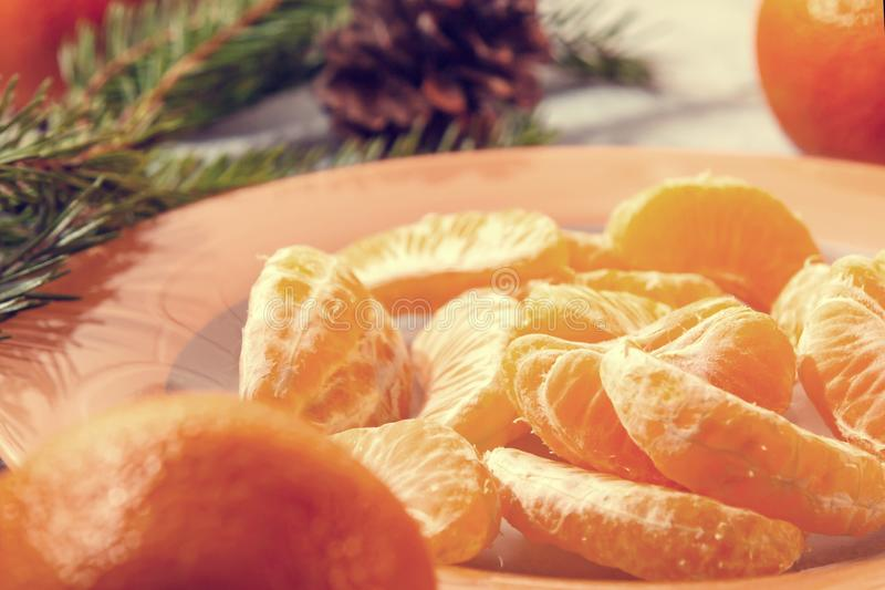 Several peeled tangerine slices on an orange plate with tree branches and a cone-a traditional Christmas and new year`s royalty free stock images