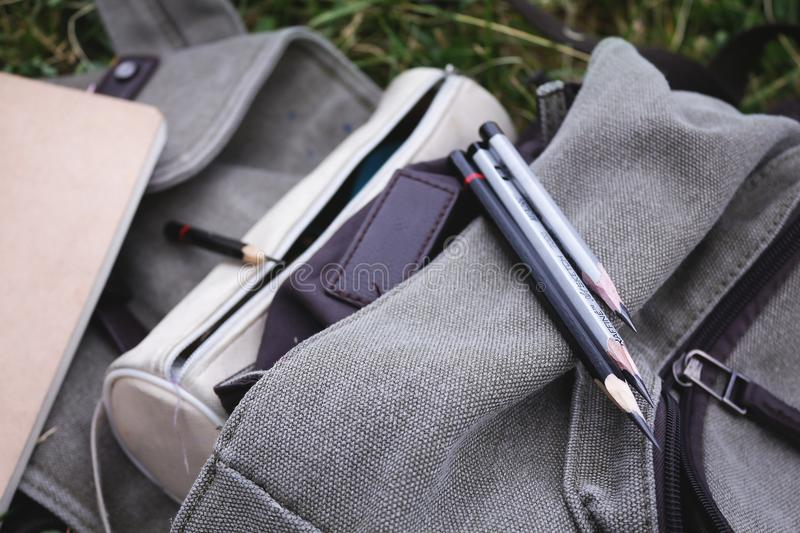 A several pencils on the gray backpack on the grass stock photo