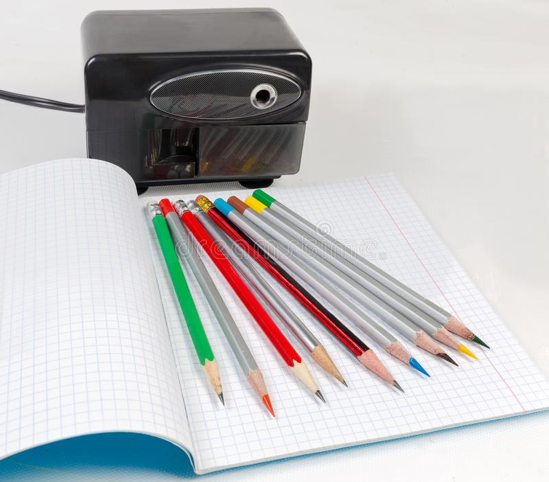 Pencils on exercise book against of desk electric pencil sharpener royalty free stock images