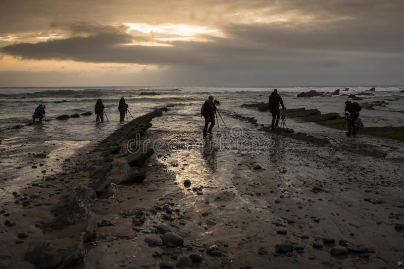 Several photographers `fish` photos on the rocky beach at sunset. On the Basque coast there are many beaches like this one, with a rocky bed that is exposed when stock photos