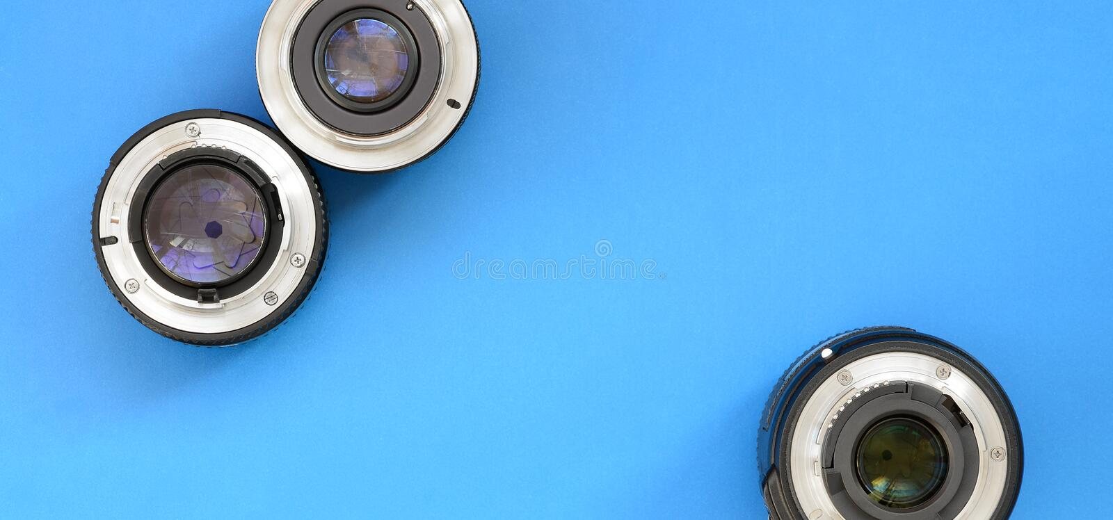 Several photographic lenses lie on a bright blue background. Spa stock photo