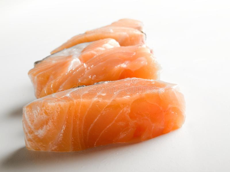 Several pieces of fresh salmon seen frontally. And placed on a white table and background stock photos