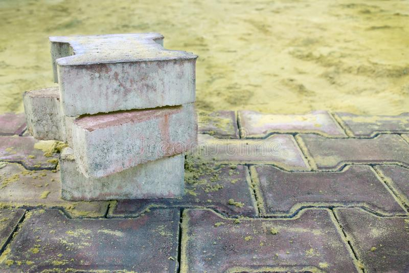 Several pieces of paving slabs lie in the place of repair of the sidewalk, road, square, on the background of sand. laying of. Paving slabs. paving slab royalty free stock photo