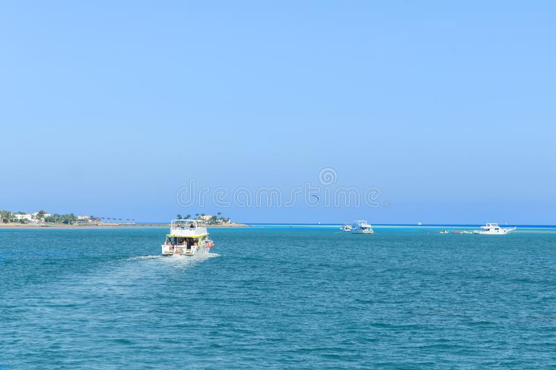 Several pleasure boats in the sea near the islands. boats in beautiful turquoise ocean near an island.  stock photo