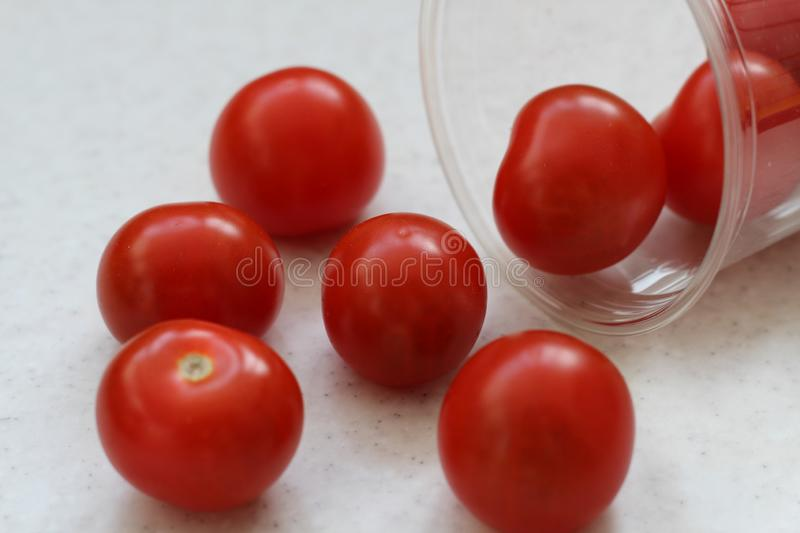 Several red ripe cherry tomatoes rolled out of a plastic transparent glass royalty free stock photos