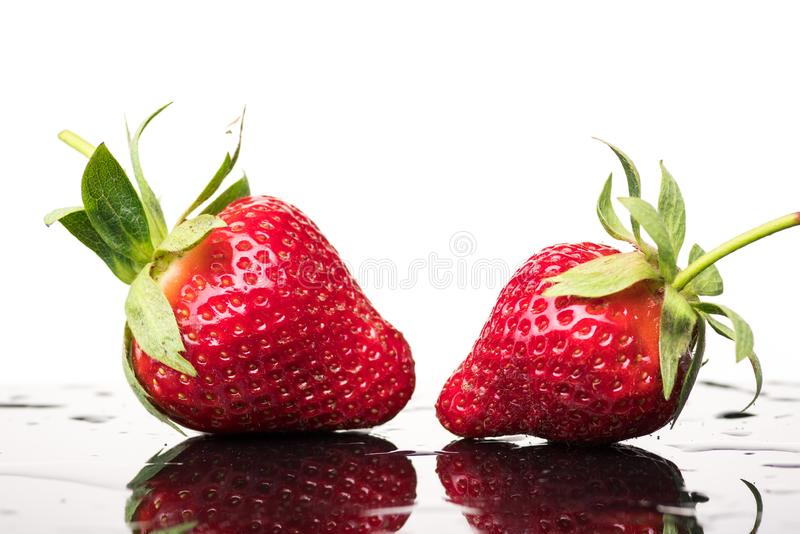 Several ripe wet red strawberries on white or colored background with splashes of water royalty free stock photo