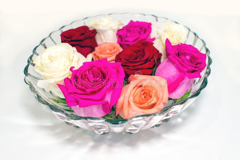 Several rose blossoms in retro glass bowl royalty free stock image