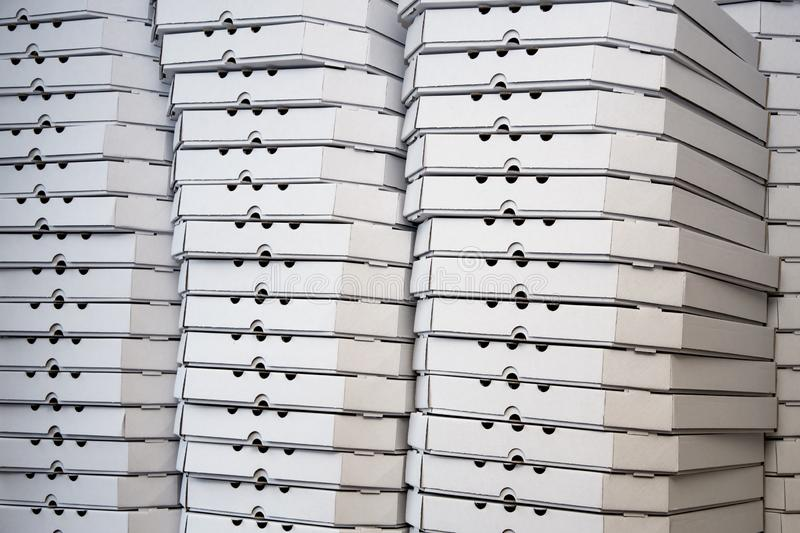 Several rows of pizza boxes, white pizza packing containers royalty free stock image