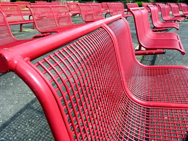 Several rows of seats with red metal chairs. Red painted iron chairs, outdoor seating opportunities, public seats for concert, comfortable ergonomic metal chairs royalty free stock image