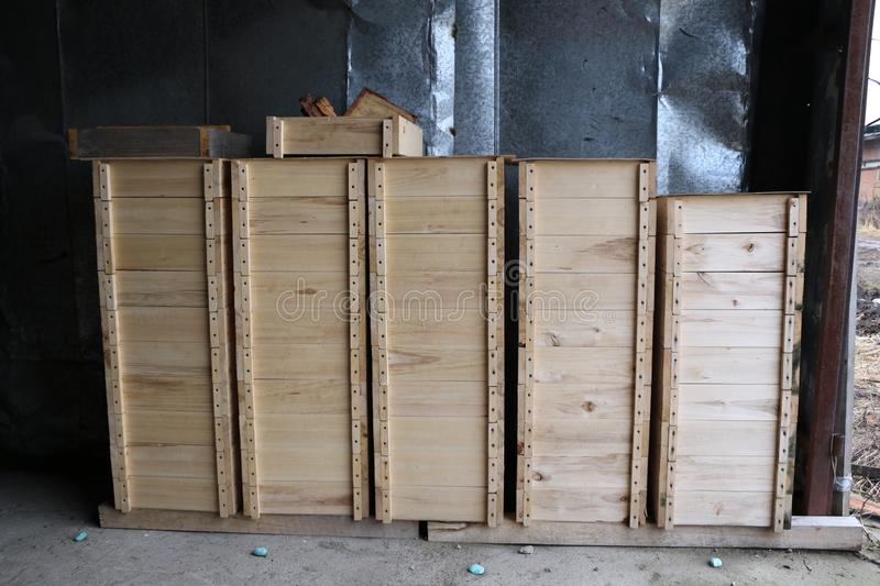 Wooden boxes for internal bee hives on a large apiary. Several rows of wooden boxes for the internal arrangement of bee hives on a large apiary stock images