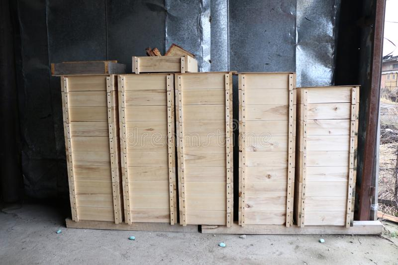 Wooden boxes for internal bee hives on a large apiary. Several rows of wooden boxes for the internal arrangement of bee hives on a large apiary stock image