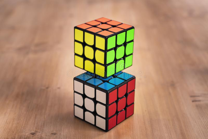 Madrid, Spain; 9 february 2019: Several Rubik cubes intelligence toys solved, in a wood table stock photo