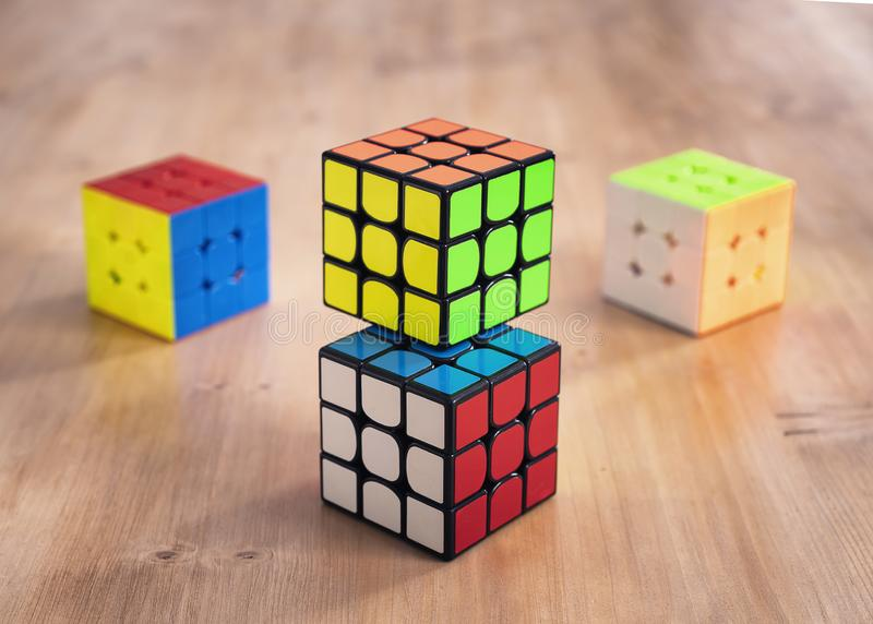 Madrid, Spain; 9 february 2019: Several Rubik cubes intelligence toys solved, in a wood table royalty free stock photos