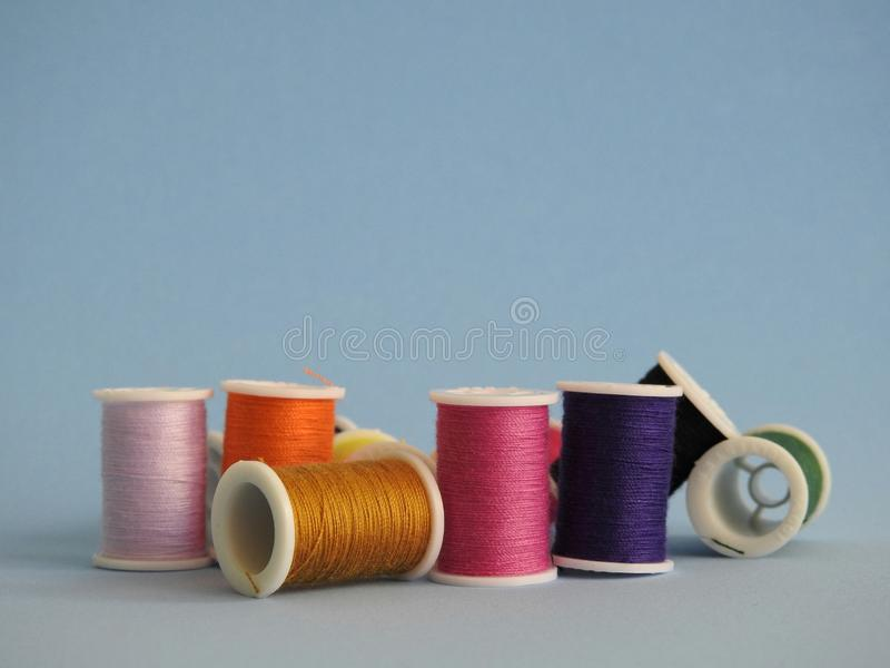 Several sewing thread spool, of varied colors. Several sewing thread spools, of varied colors. Some are standing and others fallen. Blue background royalty free stock photo