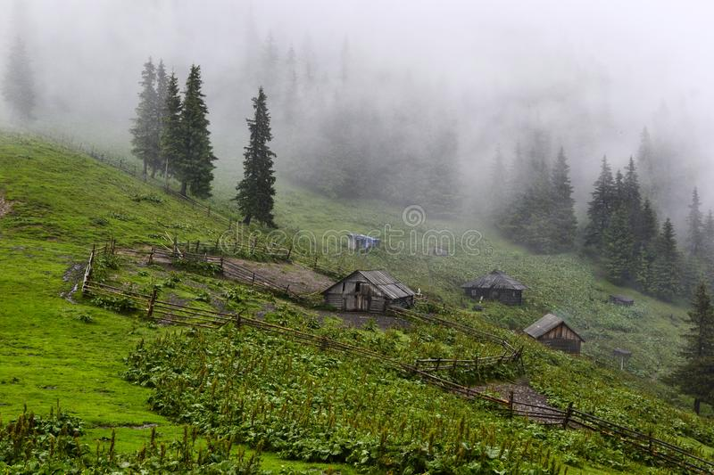 Several shepherds houses in the mountains. Rainy weather with clouds and fog. Carpathians, Ukraine stock photos