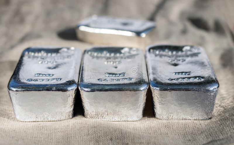 Several silver bars against the background of the texture of coarse cloth. Selective focus stock image