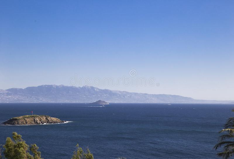 Several small islands in the sea and mountains in the backgroun. View of several small islands in the sea and mountains in the background in the morning haze stock photos