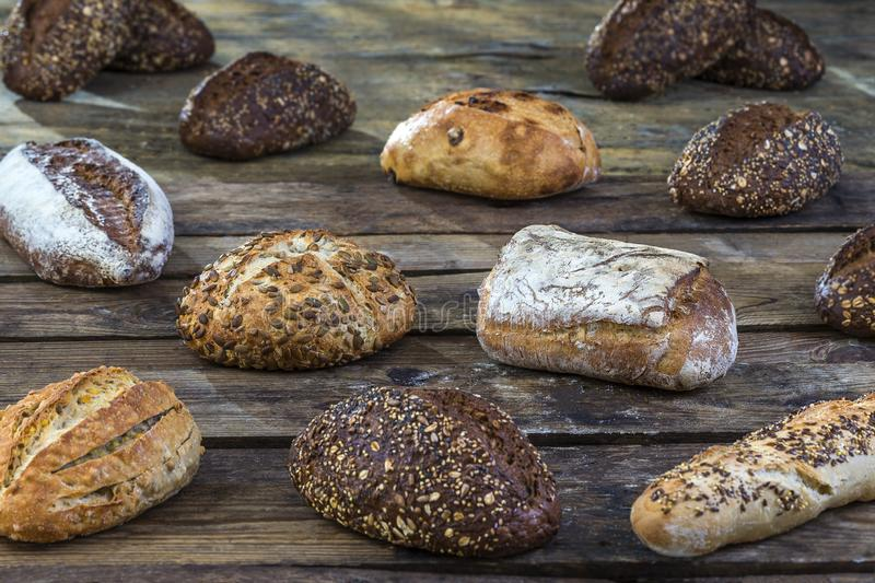 Several small multi grain different shaped bread sprinkled with whole sunflower seeds, flax and sesame seeds and wheat. Several small multi grain triangular royalty free stock images