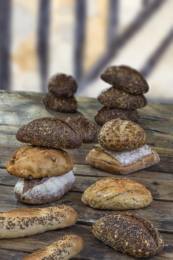 Several small multi grain different shaped bread sprinkled with whole sunflower seeds, flax and sesame seeds and wheat stock images