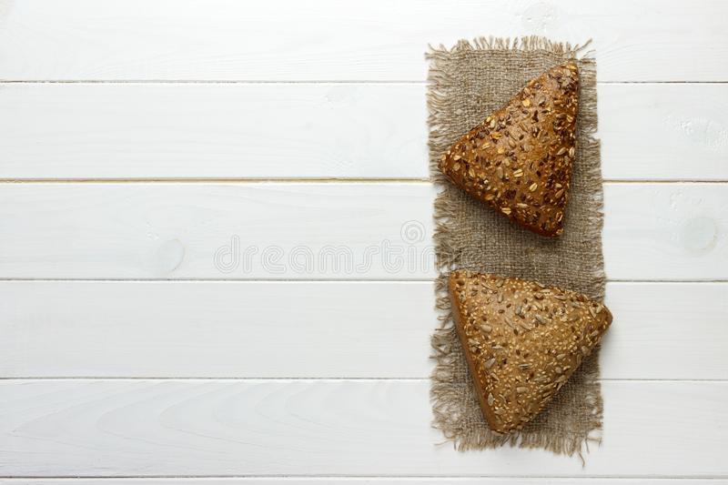 Several small multi grain triangular shaped bread sprinkled with whole sunflower seeds, flax and sesame seeds on a sackcloth.  stock images
