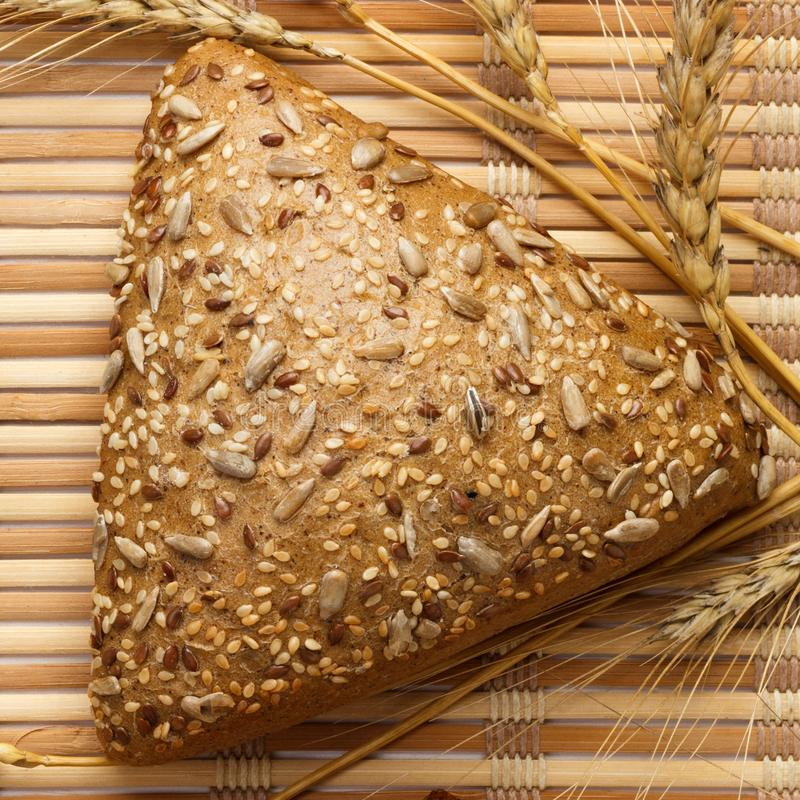 Several small multi grain triangular shaped bread sprinkled with whole sunflower seeds, flax and sesame seeds and wheat and barley. Spikes stock images