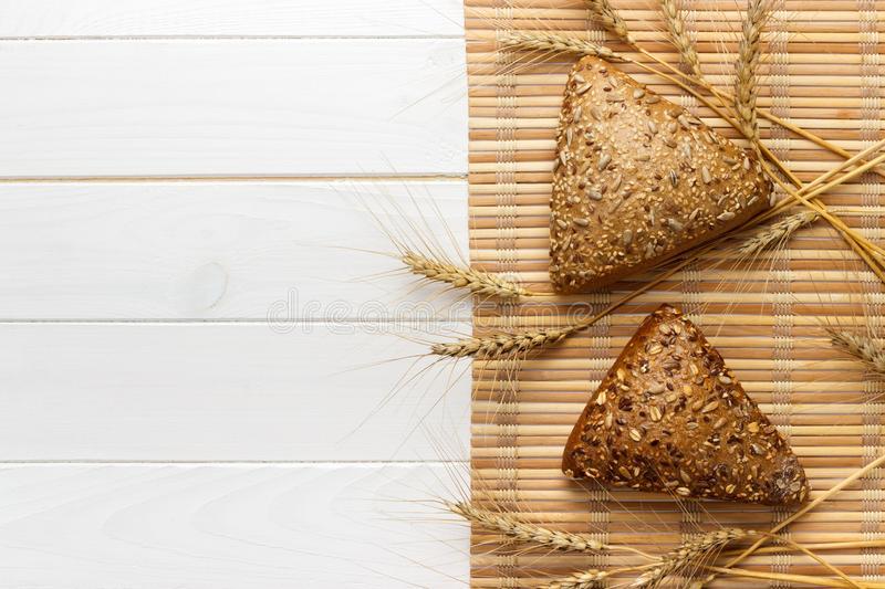 Several small multi grain triangular shaped bread sprinkled with whole sunflower seeds, flax and sesame seeds and wheat and barley. Spikes stock photography