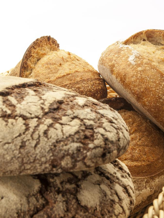 Several stacked artisan loaves viewed frontally. On a white background stock image