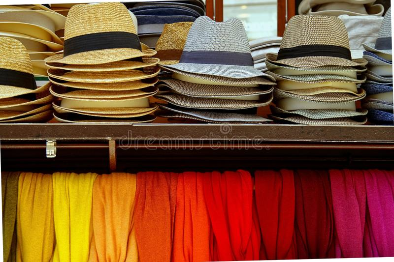 Several straw hats and colorful scarves for sale at an outdoor market in Verona, Italy. stock photography