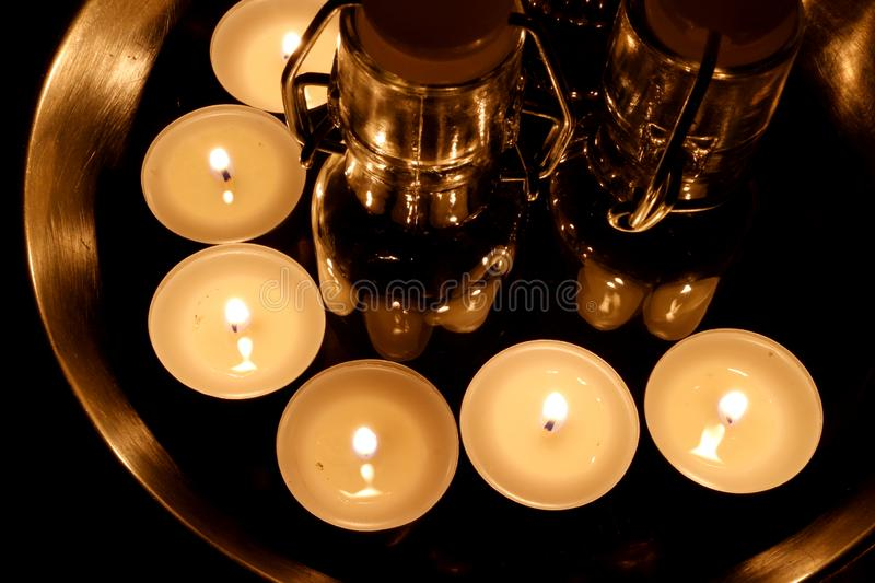 Several lit tea lights stands on a metallic surface around tiny glass bottles stock photos