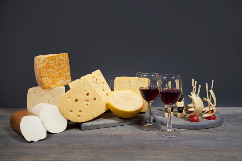 Several varieties of cheese on a wooden board, glasses with red wine and skewers with appetizers royalty free stock photo