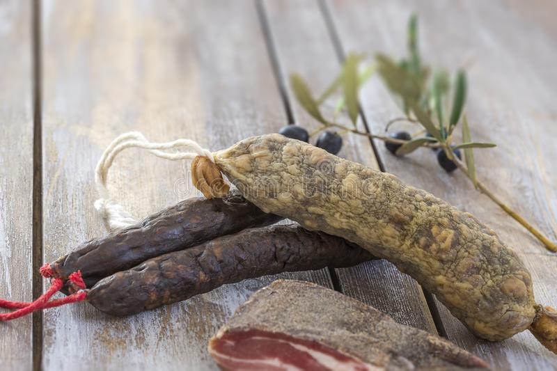 Several variety of traditional Corsican charcuterie with an olive branch and black olives on wooden background. Several variety of traditional Corsican stock images