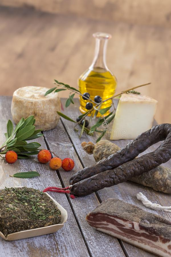 Several variety of traditional Corsican charcuterie with an olive branch and black olives on wooden background. Several variety of traditional Corsican stock photos