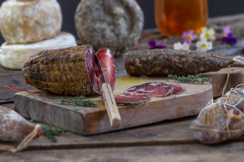 Several variety of traditional Corsican charcuterie with an olive branch and black olives on wooden background. Several variety of traditional Corsican stock image
