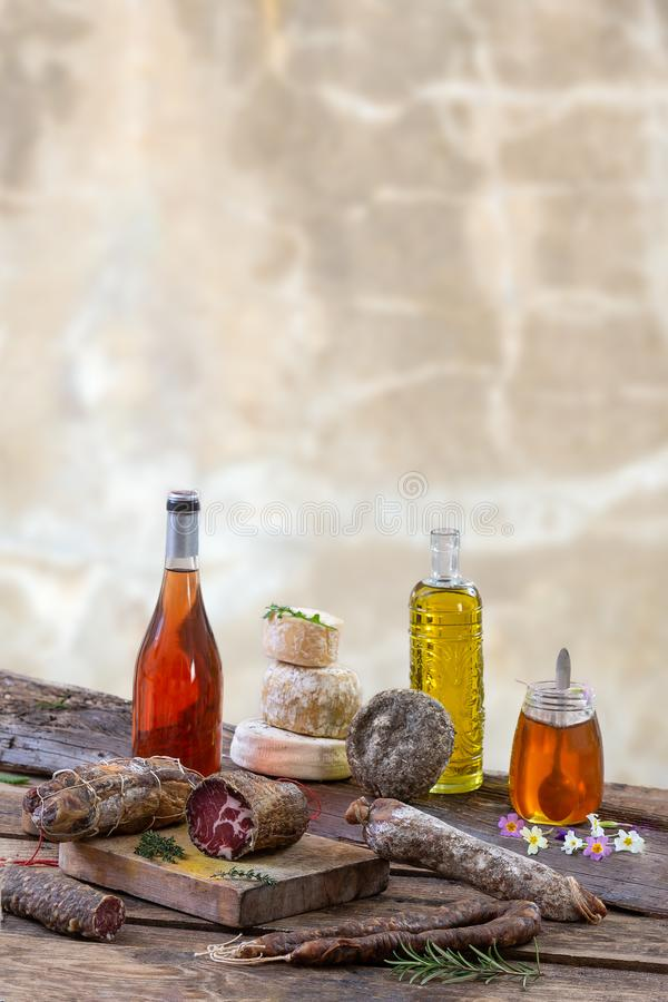 Several variety of traditional Corsican charcuterie with an olive branch and black olives on wooden background. Several variety of traditional Corsican stock photography